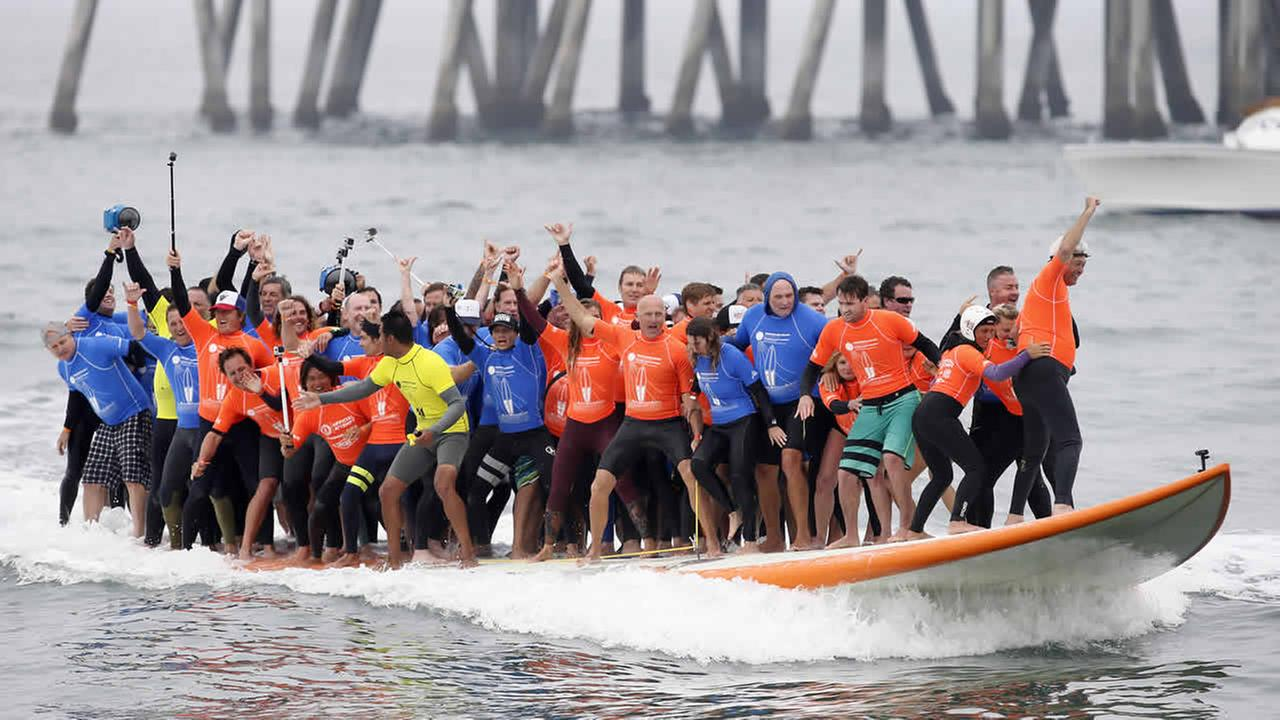 Sixty-six surfers from around the world ride a custom built 42-foot, 1300 pound surfboard on June 20, 2015 in Huntington Beach, CA. (Danny Moloshok/AP Images for Visiting Huntington Beach)