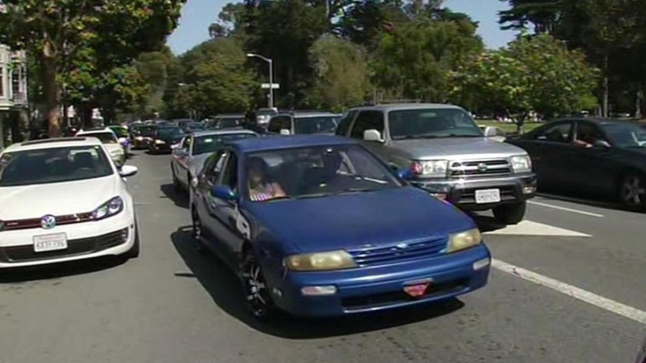 blue car driving down a street in San Francisco