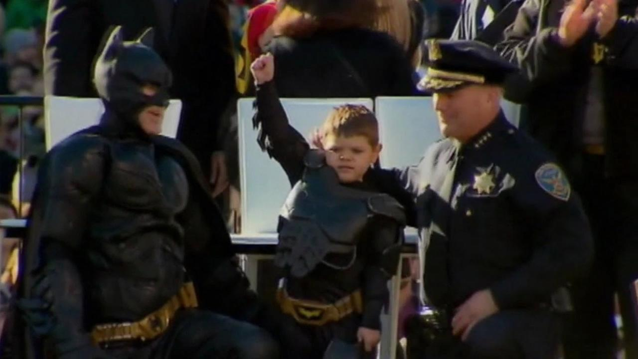 Miles Scott, dressed as Batkid, raises his fist in the air at San Francisco City Hall on Friday, Nov. 15, 2013.
