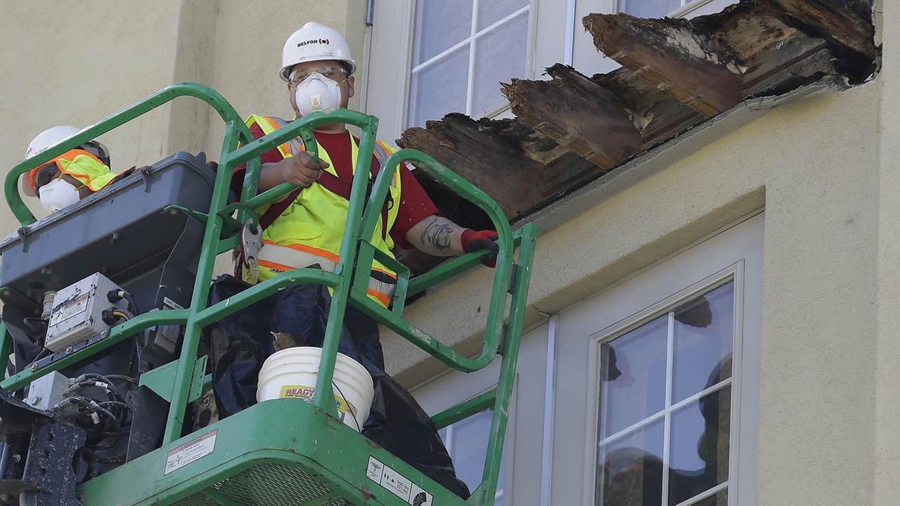 FILE - In this June 18, 2015, file photo, a crew works on the remaining wood of an apartment building balcony that collapsed in Berkeley, Calif. (AP Photo/Jeff Chiu, File)