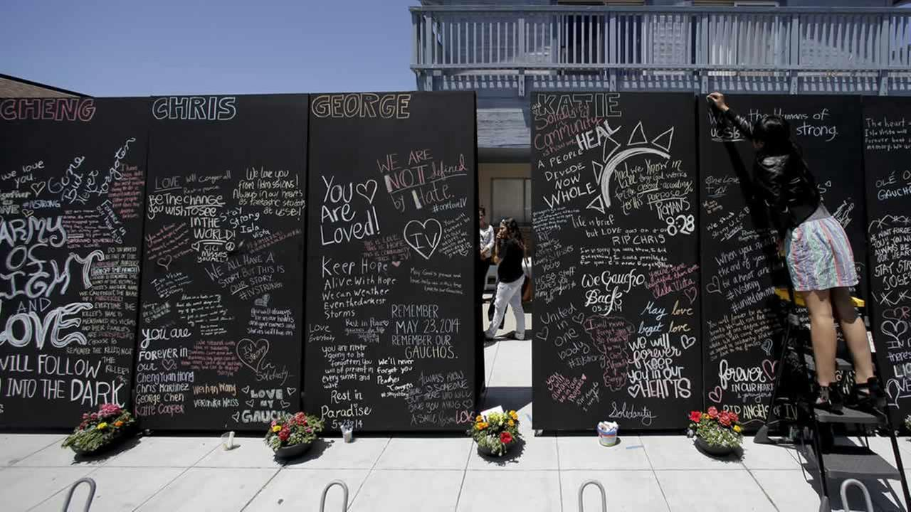 Rinda Sutrarhada, 20, writes the names of the victims on a remembrance wall across the street from the IV Deli Mart in the Isla Vista, Calif. (AP Photo/Chris Carlson)