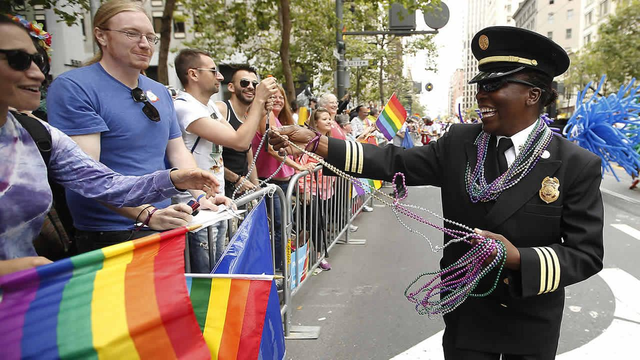 San Francisco Fire Departments Deputy Chief Raemona Williams passes out beaded necklaces to the crowd during the Pride parade on June 28, 2015, in San Francisco. (AP Photo/ Tony Avelar)