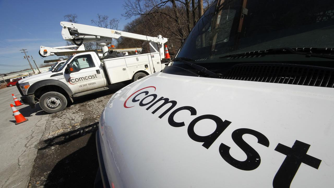 FILE - In this Feb. 15, 2011 file photo, Comcast logos are displayed on installation trucks in Pittsburgh.