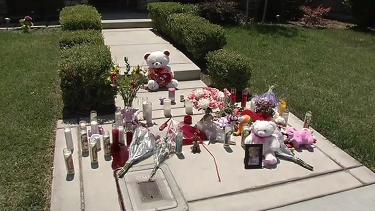 Candles and flowers are left outside a Modesto, Calif. home where two women and three young girls were found dead on July 18, 2015.