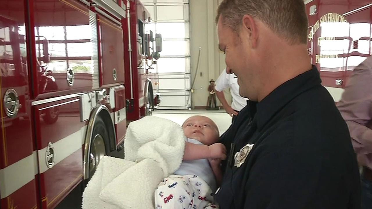 firefighter Jesse Lange holds Alexis Mendezs baby