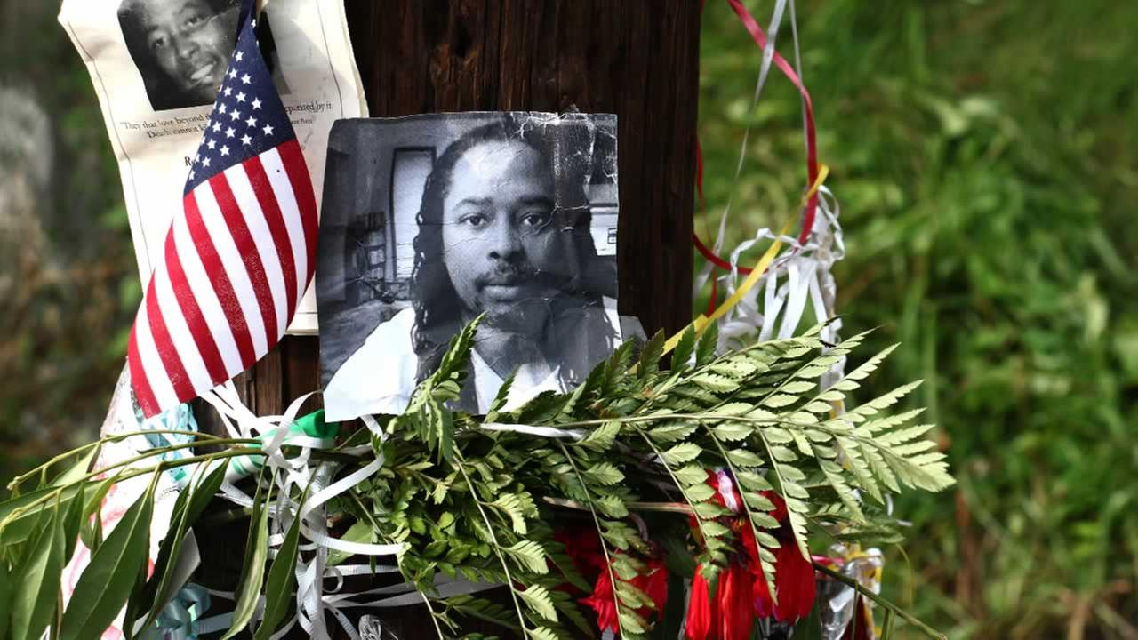 Photos of Samuel DuBose hang on a pole at a memorial, Wednesday July 29, 2015 in Cincinnati, near where he was shot and killed by a University of Cincinnati police officer.