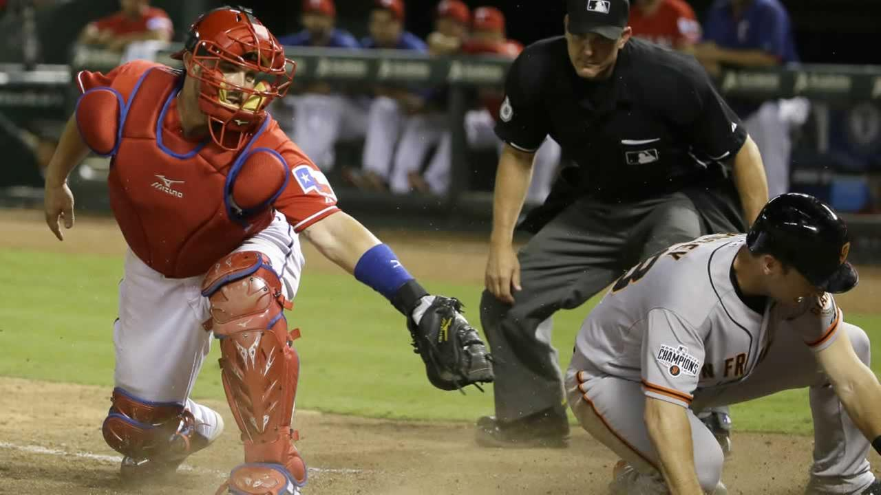 Giants Buster Posey  slides safely into home plate to score as Texas Rangers catcher Bobby Wilson fields the late throw in Arlington, Texas, Saturday, August 1, 2015.
