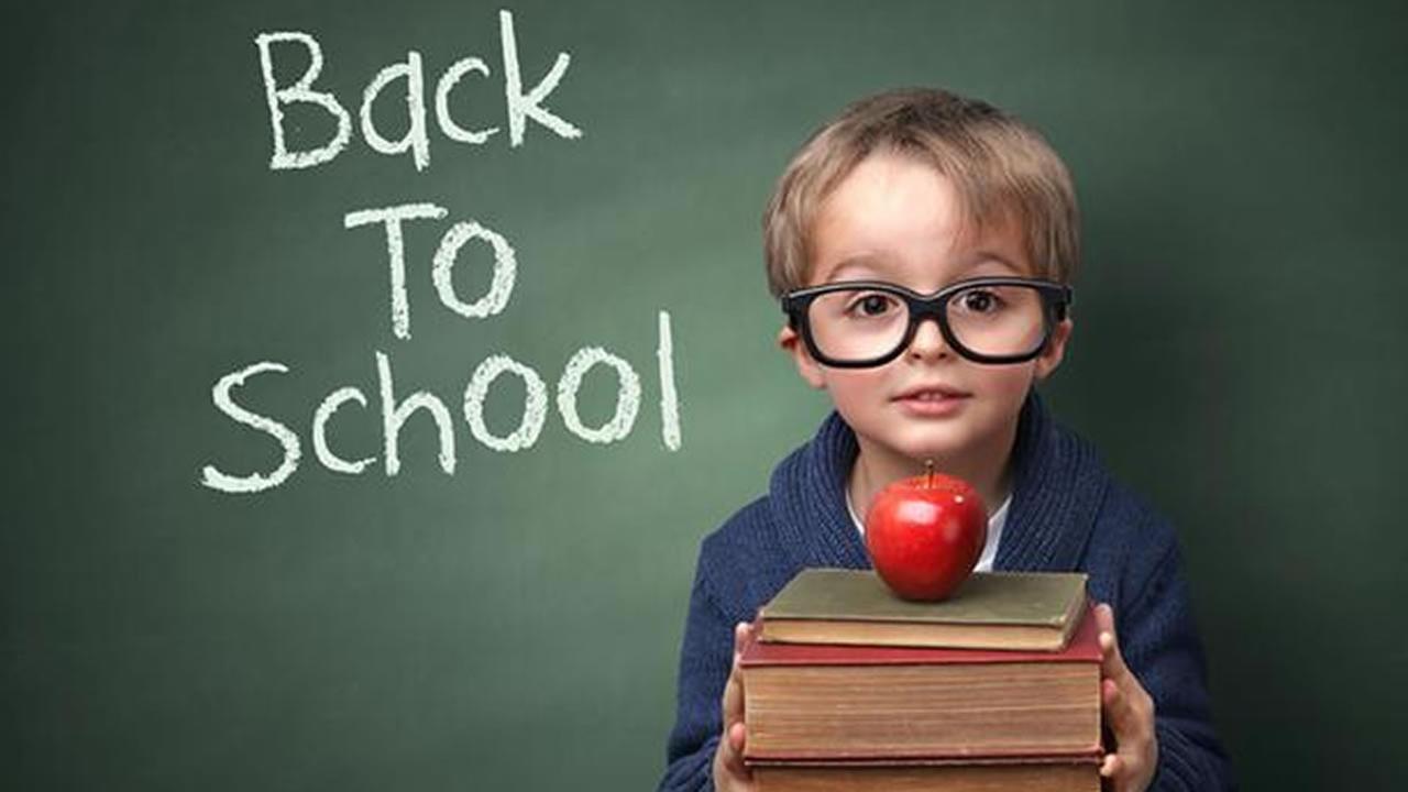 child holds books, back to school written on chalkboard.
