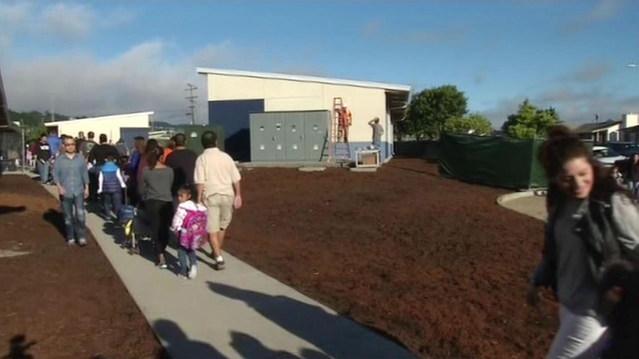 Parents escort their children through Biri Biri Elementary School in South San Francisco on the first day of school, August 12, 2015.