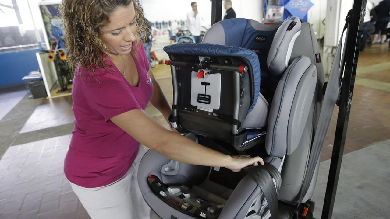 In this May 16, 2015 photo, Kate Clark, Public Relations and Events Manager at Britax, demonstrates how to install the Click Tight infant car seat at the New York Baby Show.