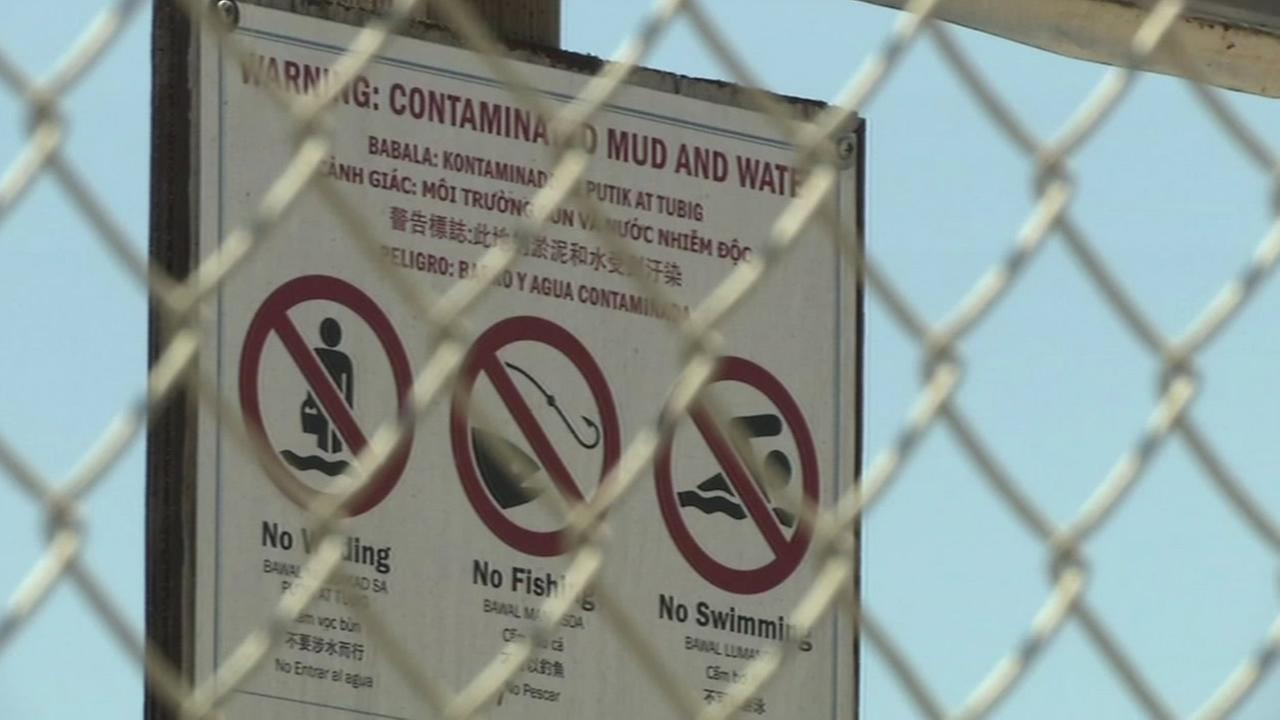 This undated image shows a sign warning of contaminated mud and water.