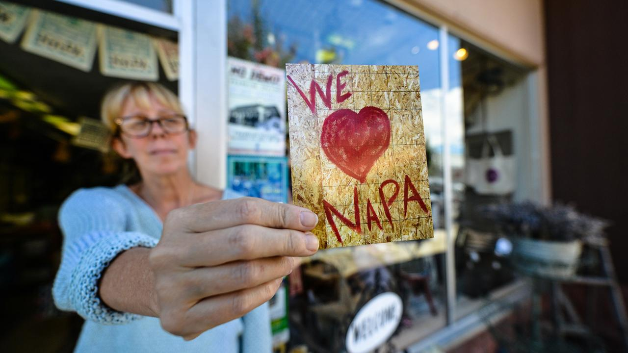On August 11, 2015, Patricia Trimble holds a postcard that helped pay for a quake-damaged window in her Napa, Calif. store. She took a photo, made the card, and sold them for $1.