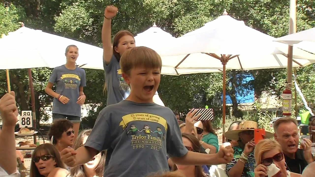 A boy sings along to Journeys Dont Stop Believing during The Taylor Family Foundations Day in the Park fundraiser in Livermore, Calif. on Sunday, August 30, 2015.