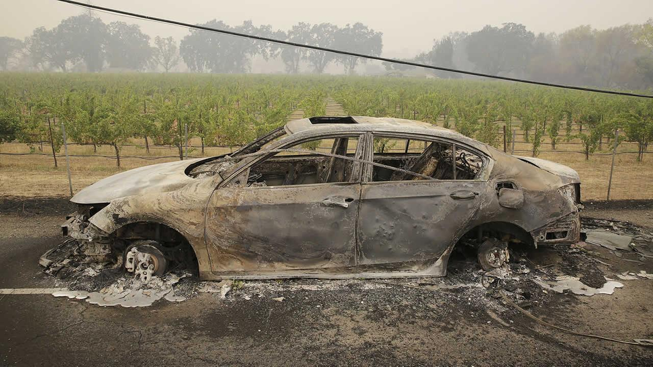 A burned car sits along Highway 29 with a vineyard in the background Sunday, Sept. 13, 2015, in Middletown, Calif. (AP Photo/Eric Risberg)