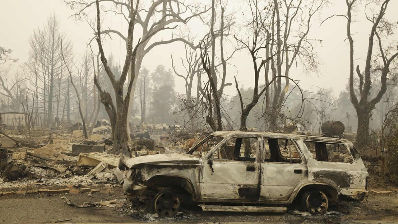A burned car sits on a street outside a number of home destroyed by fire Sunday, Sept. 13, 2015, in Middletown, Calif. (AP Photo/Eric Risberg)