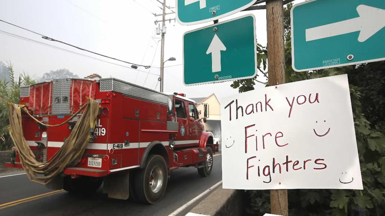 Firefighters pass a Thank you sign in Angels Camp, Calif., on their way for another day of battling the Butte Fire, Sunday, Sept. 13, 2015.