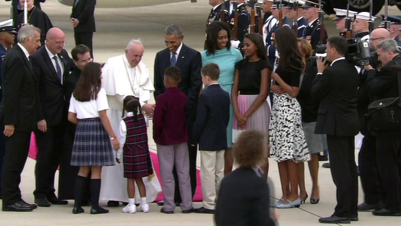 President Barack Obama and family stand nearby as Pope Francis shakes hands after arriving in Washington D.C. on Tuesday, September 22, 2015.