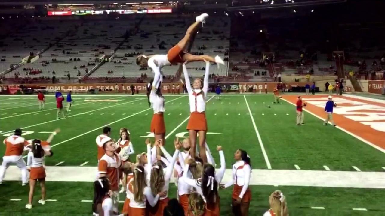 This undated image shows University of Texas cheerleading squad during a stunt on the field of Derrell K. Royal Texas Memorial Stadium in Austin.