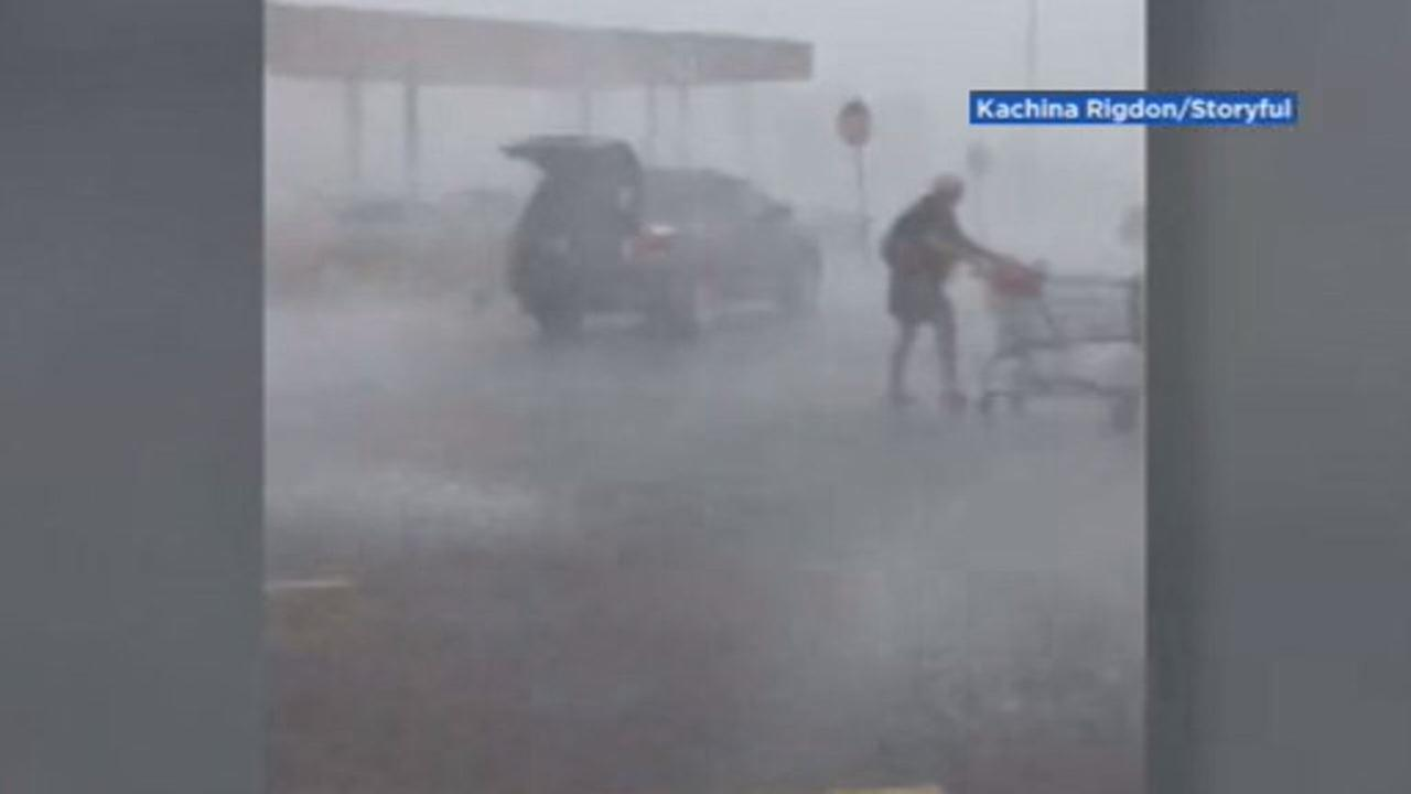 This image shows a woman braving a storm to return a grocery shopping cart to its proper place in Hurricane, West Virginia on July 31, 2018.