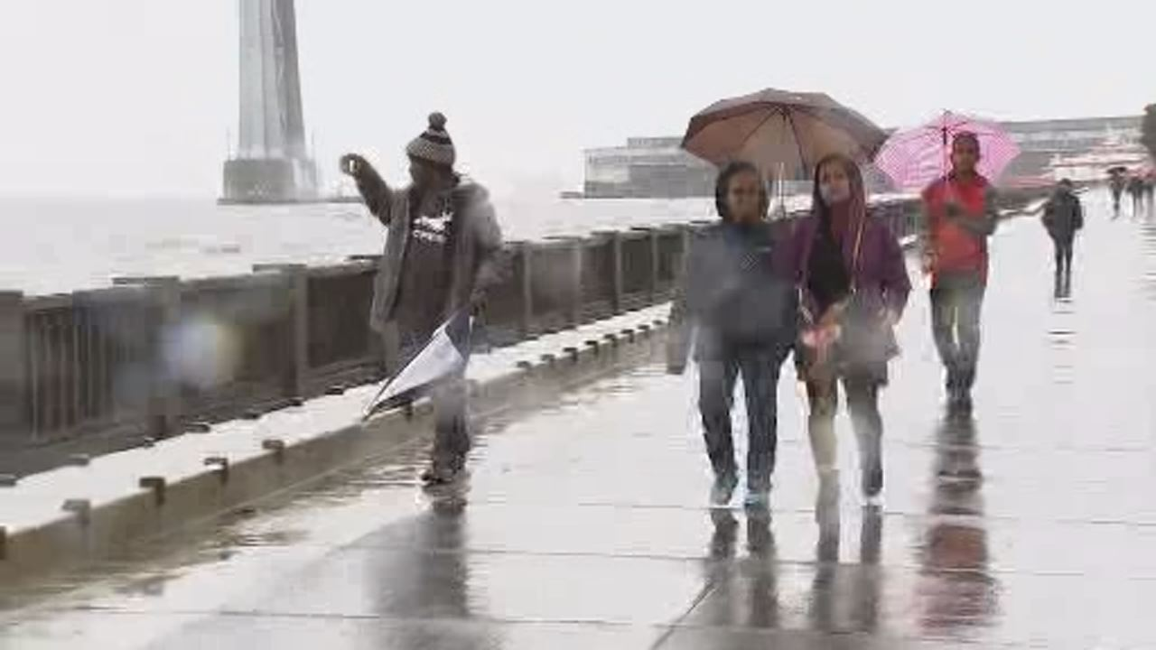 This image shows a group of people walking along San Franciscos Embarcadero during last weekends storm.