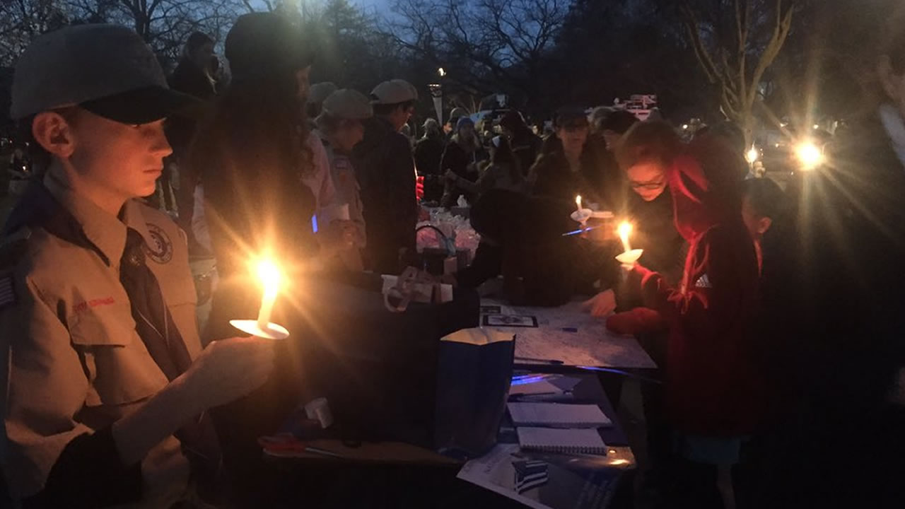 This image shows people gathered in Central Park in Davis, Calif. for a Saturday, Jan. 12, 2019 vigil for slain Officer Natalie Corona.
