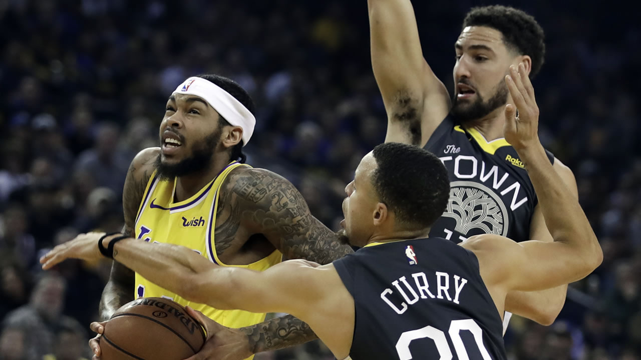 Lakers Brandon Ingram drives the ball past Warriors Stephen Curry and Klay Thompson in the first half of an NBA basketball game Saturday, Feb. 2, 2019, in Oakland, Calif.