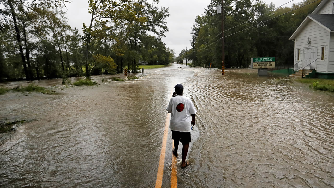 Helen McKoy walks down a flooded street in her neighborhood as Florence continues to dump heavy rain in Fayetteville, N.C., Sunday, Sept. 16, 2018.