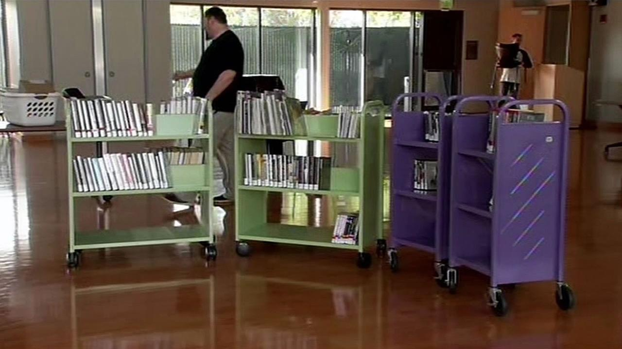 FILE - A man walks past a book case at the Mitchel Park Library in Palo Alto in this undated image.