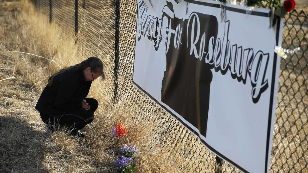 Robin Griffiths, of Portland, prays at a makeshift memorial near the road leading to Umpqua Community College Saturday, Oct. 3, 2015, in Roseburg, Ore.