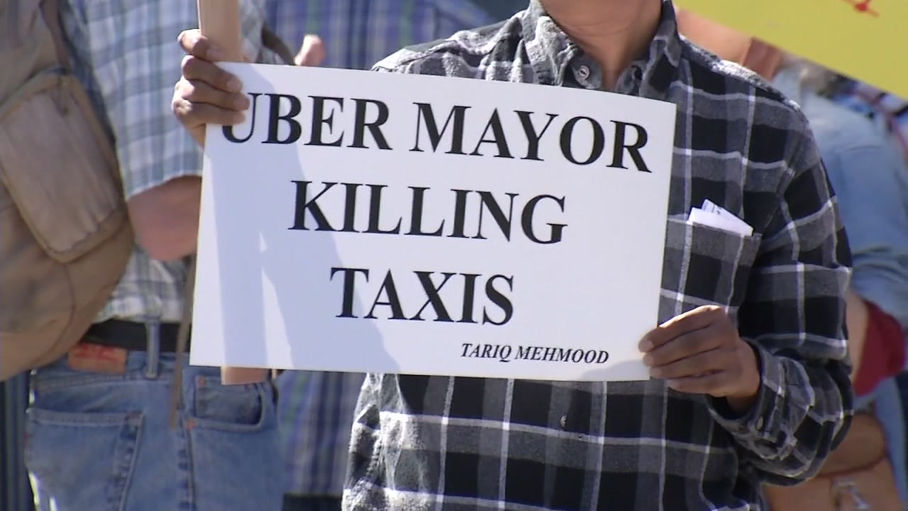 A taxi driver is seen holding a sign in protest outside city hall in San Francisco, Calif. on Tuesday, Oct. 16, 2018.