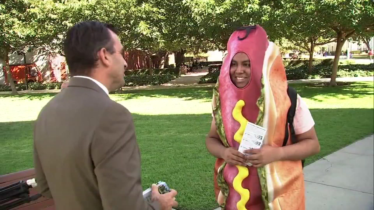 San Jose Mayor Sam Liccardo is seen talking with a person in a hot dog costume during a voter drive in San Jose, Calif. on Wednesday, Oct. 31, 2018.