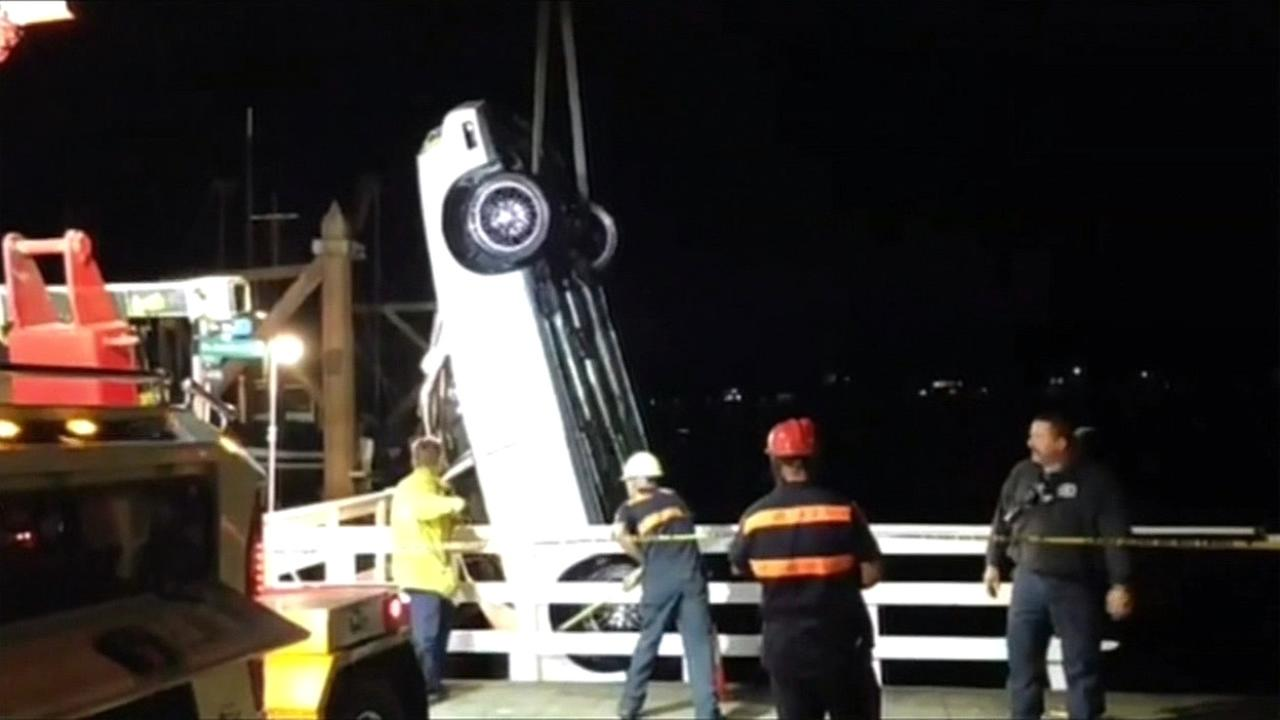 Crews towed a car out of the ocean after it crashed through a 4-foot fence at the wharf in Santa Cruz, Calif. on Saturday, October 17, 2015.