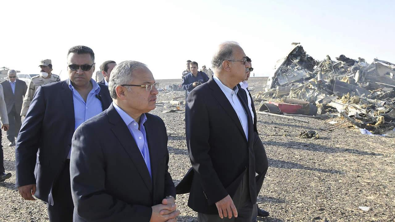 In this image released by the Prime Ministers office, Sherif Ismail, center, visits the site where a plane crashed in Hassana Egypt, Friday, Oct. 31, 2015.