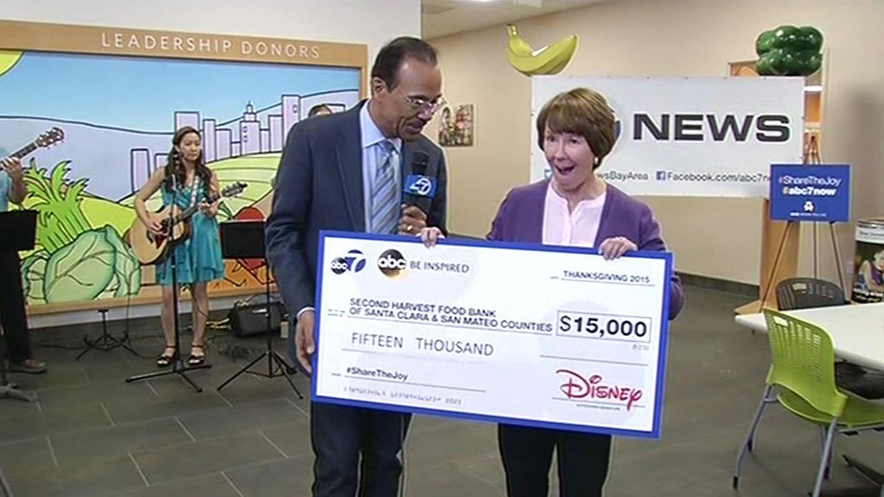 Spencer Christian presents a check for $150,000 to the CEO of Second Harvest Food Bank, Kathy Jackson, in San Jose, Calif. on Friday, November 6, 2015.