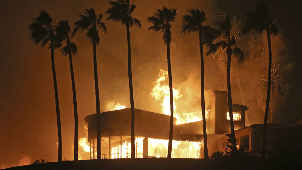 Palm trees frame a home being destroyed by a wildfire above Pacific Coast Highway in Malibu, Calif., Friday, Nov. 9, 2018.