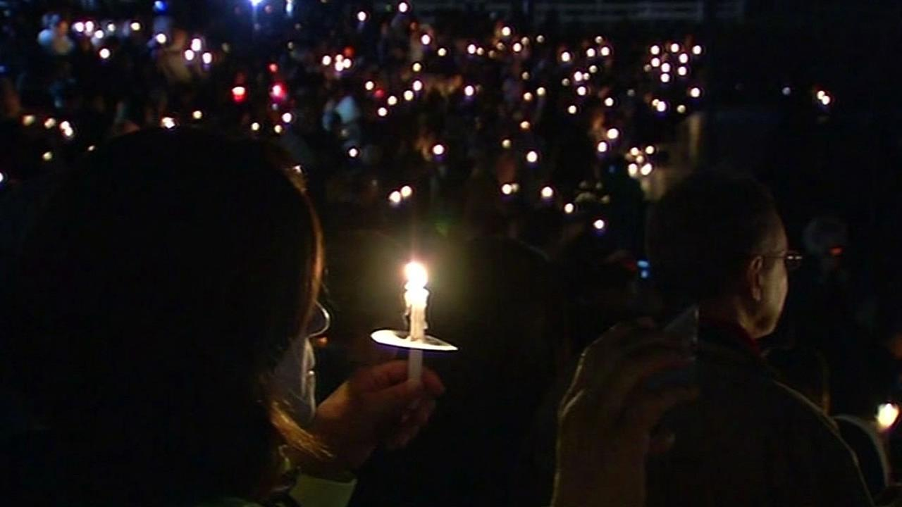 a woman holds a candle at a vigil for the San Bernardino shooting vicitms