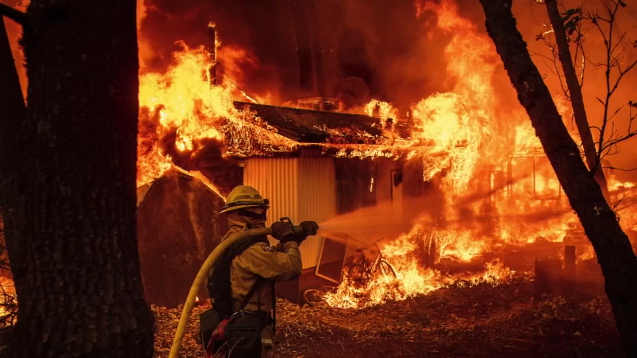 A firefighter is seen hosing down an area as flames rage during the Camp Fire in Butte County in this undated image.