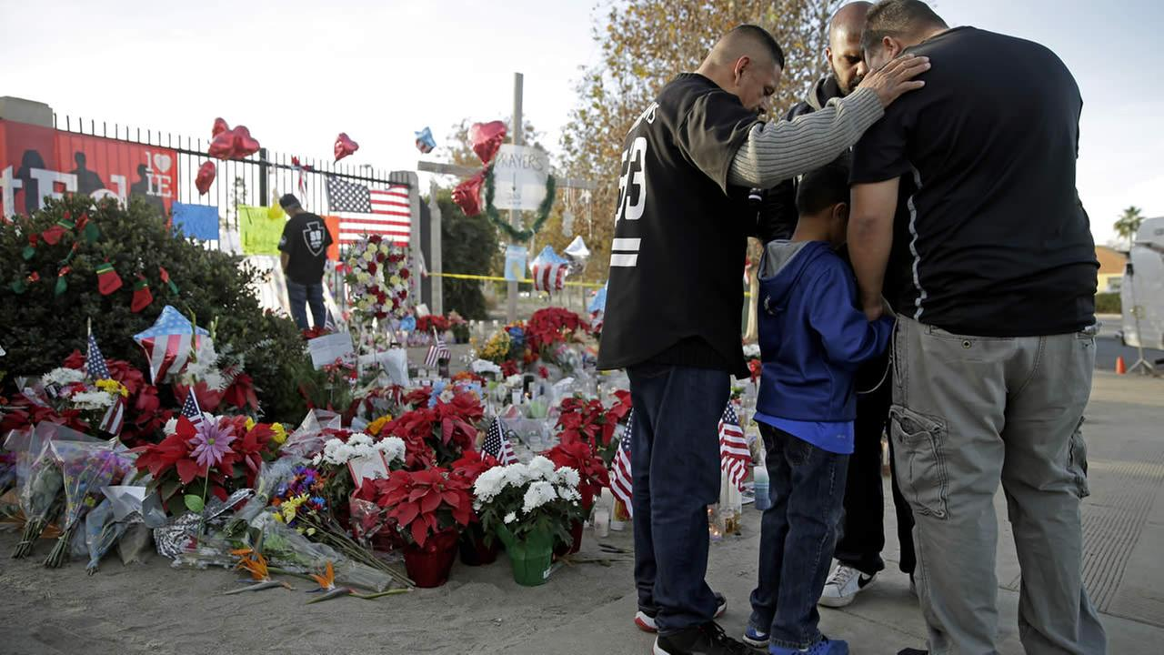 Mourners comfort each other at a makeshift memorial site honoring Wednesdays shooting victims Monday, Dec. 7, 2015 in San Bernardino, Calif. (AP Photo/Jae C. Hong)