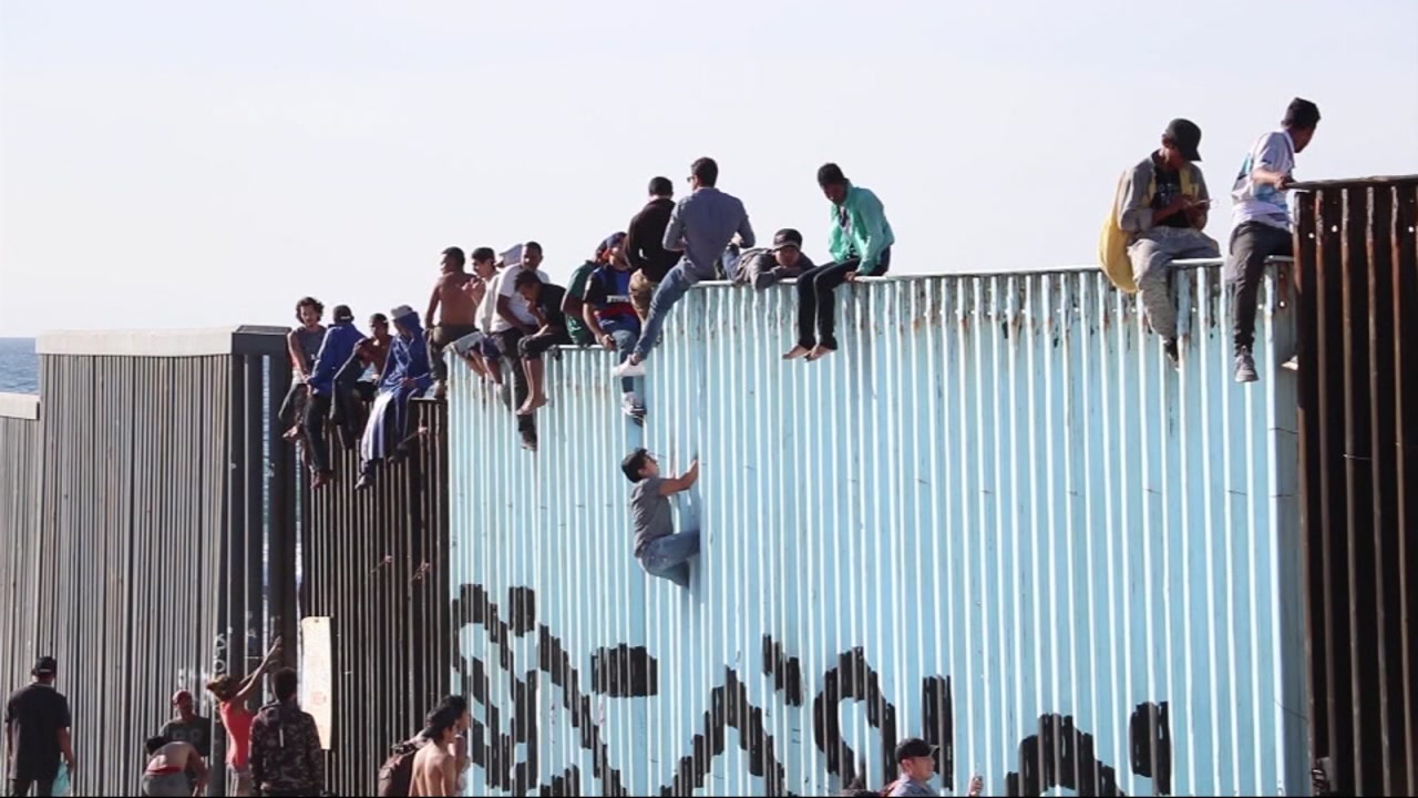 People are seen climbing and sitting on the U.S.-Mexico border wall in Tijuana on Wednesday, Nov. 14, 2018.