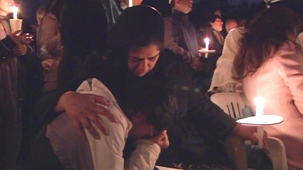 family members embrace and cry at a vigil held for Shireen Ahsan and Suleiman Nourzai