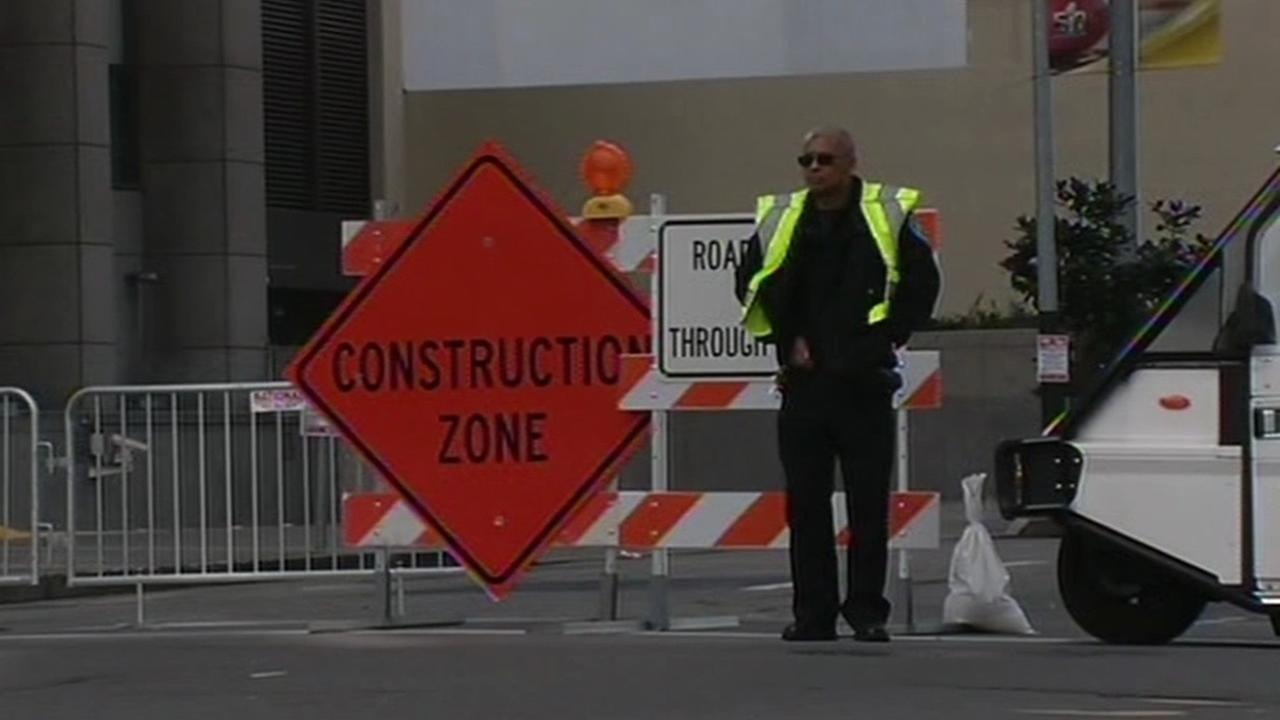 A man stands next to a construction sign as crews work on Super Bowl City in San Francisco, Calif. on Sunday, January 24, 2016.