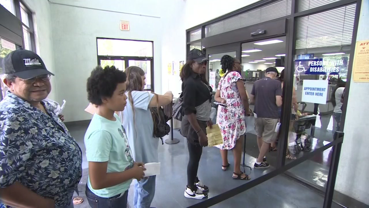 People are seen waiting at the entrance to a DMV office in this undated image.