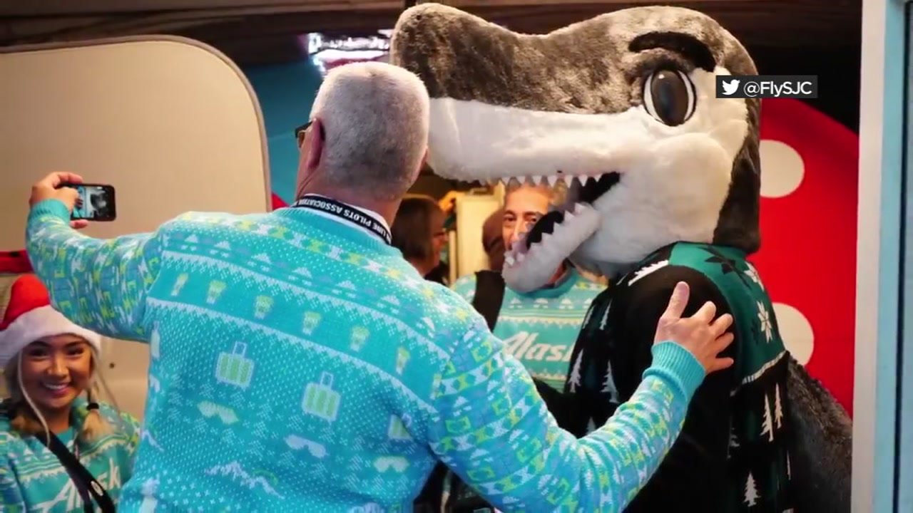 SJ Sharkie is seen taking a photo with a traveler at the San Jose International Airport on Friday, Dec. 21, 2018.