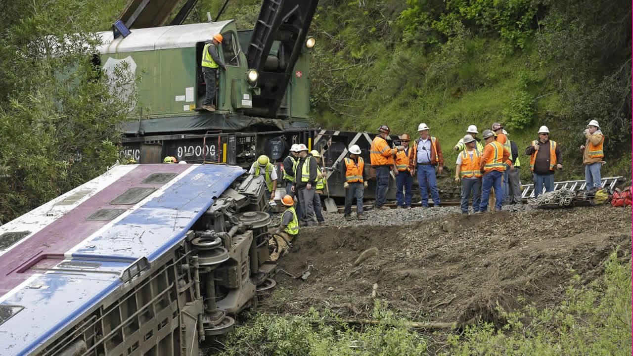 Workers connect a derailed Altamont Corridor Express train to a crane to remove it from Alameda Creek Tuesday, March 8, 2016, in Sunol, Calif. (AP Photo/Ben Margot)