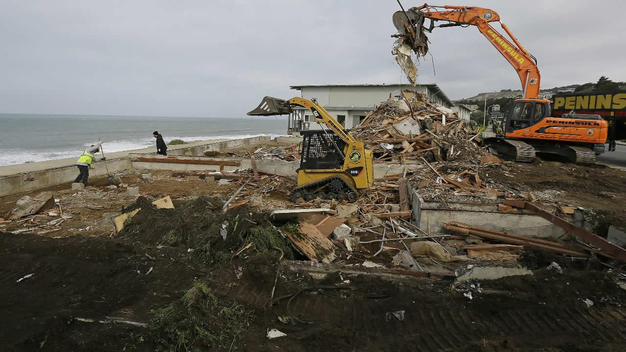 A crew clears away debris from a demolished cliffside apartment that massive erosion had left teetering on the edge of a cliff overlooking the Pacific Ocean, Friday, Feb. 19, 2016, in Pacifica, Calif.