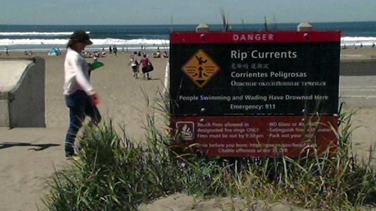A woman walks past a beach warning sign at Ocean Beach in San Francisco, Calif. on Sunday, April 17, 2016.