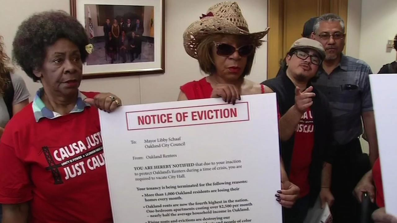 A group of demonstrators hold up signs against Oaklands skyrocketing rent prices.