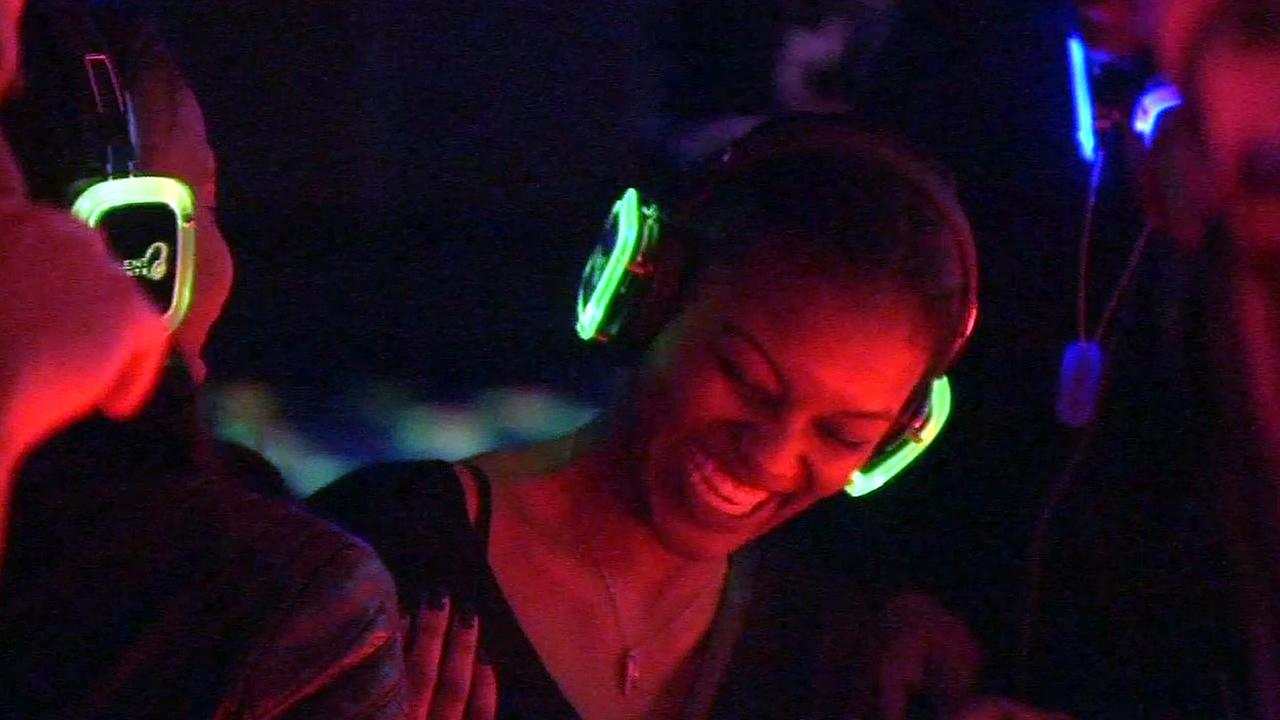 A woman wearing headphones is smiling as she takes part in a Silent Disco in this undated image.
