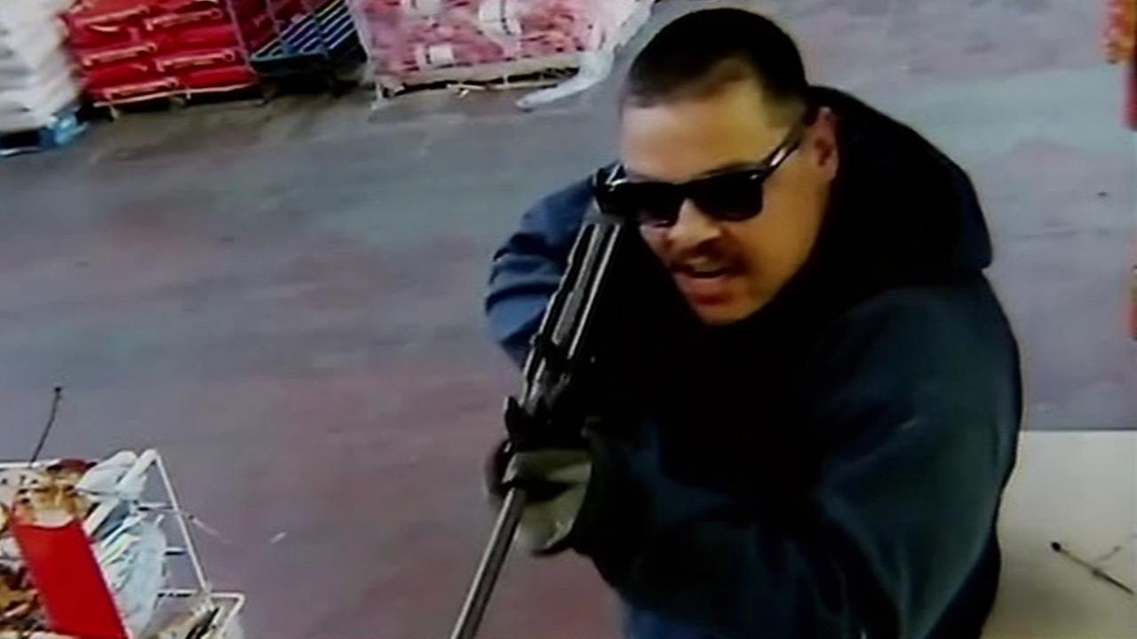 A robbery suspect is seen holding a gun at an HP Foods store in San Jose, Calif. in this undated image.