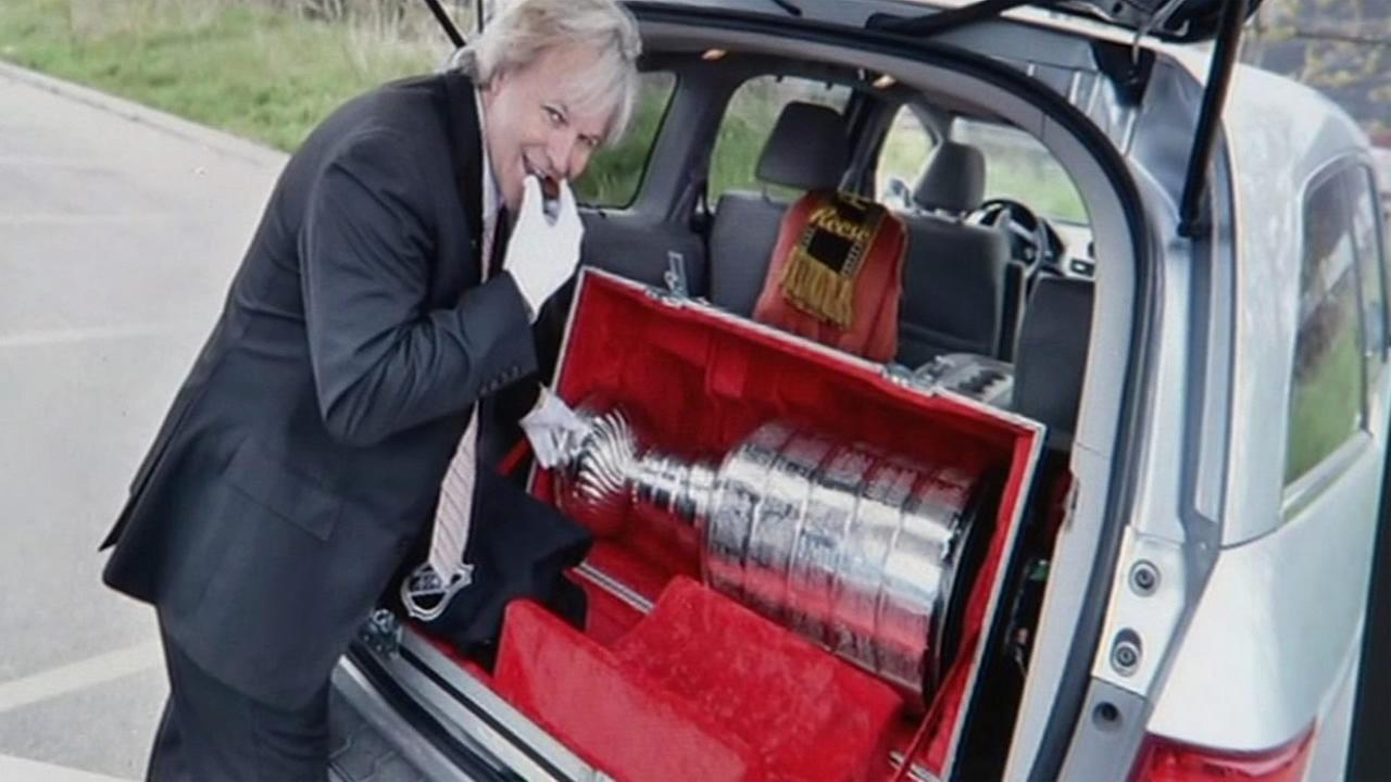 The keeper of the Stanley Cup, Phil Pritchard, is seen smiling next to it in this undated image.